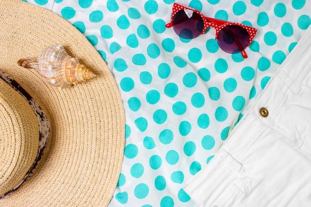 Chapeau de paille pour femme, lunettes de soleil, vue de dessus, coquillage, short avec un espace pour le texte.