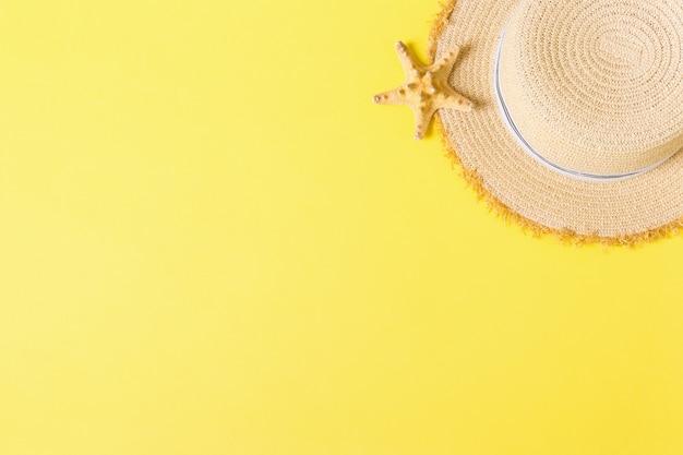 Chapeau de paille rétro jaune avec vue de dessus seastar avec espace de copie. concept d'été sur fond jaune.