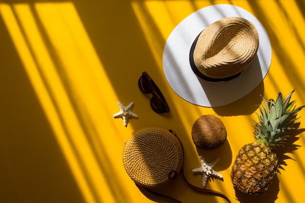 Chapeau de paille, sac en bambou, lunettes de soleil, noix de coco, ananas, étoile de mer