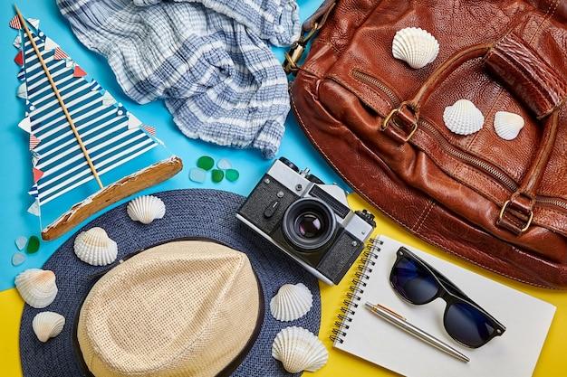 Chapeau de paille, sac de voyage, lunettes de soleil, cahier, voilier fait main et appareil photo