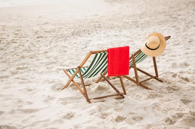 Chapeau de paille et serviette conservés sur des chaises de plage