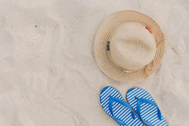 Chapeau de paille et tongs sur une plage tropicale