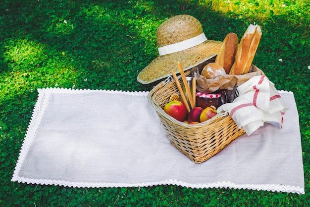 Chapeau, panier de paille avec nourriture et boissons sur plaid beige.
