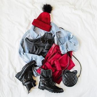 Chapeau et pantalon d'hiver vineux avec veste en jean bleu, sac à main et bottes sur drap blanc. tenue élégante d'automne ou d'hiver pour femmes. collage de vêtements à la mode. mise à plat, vue de dessus.