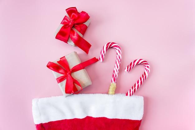 Chapeau de père noël avec boîte-cadeau et personnel caramel sur fond rose.
