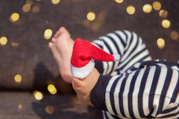 Chapeau de père noël sur le pied du bébé avec des lumières décoratives sur le fond