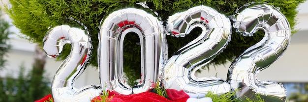 Chapeau de père noël rouge et ballons argentés avec des nombres suspendus à un arbre de noël vert en gros plan
