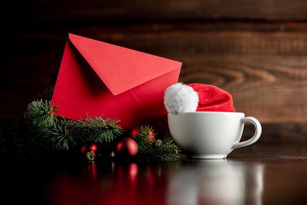 Chapeau de père noël et tasse avec enveloppe