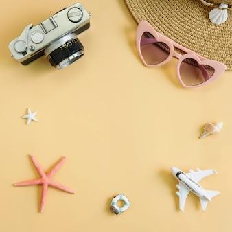 Chapeau de plage avec articles de caméra et de voyage sur fond jaune
