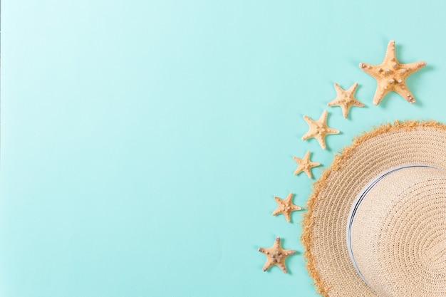 Chapeau de plage avec coquillages sur table bleu marron. concept de fond d'été avec vue de dessus de l'espace de copie.