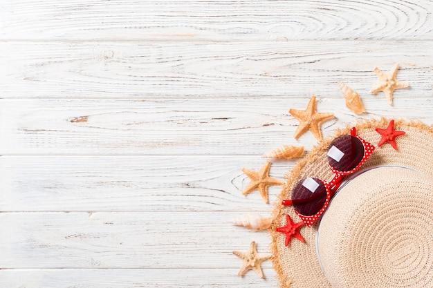 Chapeau de plage avec coquillages sur table en bois marron. concept de fond d'été avec vue de dessus de l'espace de copie.