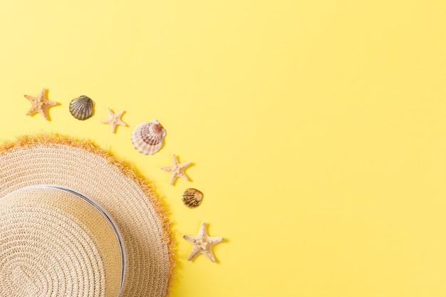 Chapeau de plage avec coquillages sur table jaune marron. concept de fond d'été avec vue de dessus de l'espace de copie.
