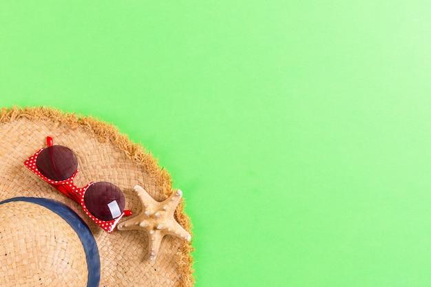 Chapeau de plage avec coquillages sur table vert marron. concept de fond d'été avec vue de dessus de l'espace de copie.