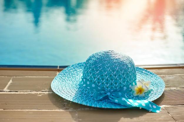 Chapeau de plage à côté de la piscine d'été au soleil couchant
