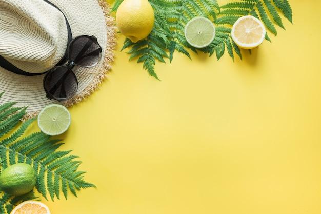 Chapeau de plage femme paille, lunettes de soleil, agrumes sur jaune.