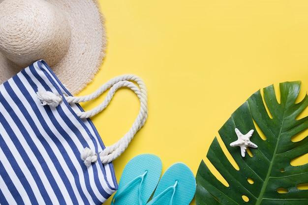 Chapeau de plage femme en paille, tenue, tongs sur jaune.