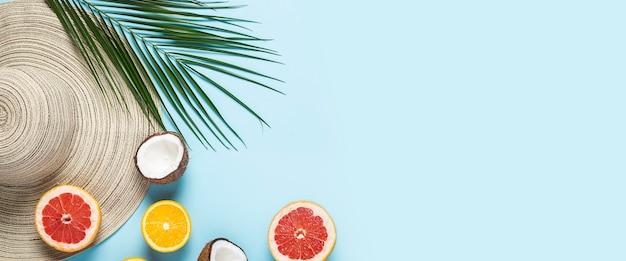 Chapeau pour femme à large bord, fruits tropicaux et branche de palmier sur fond bleu.