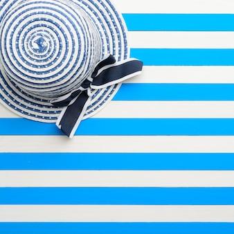 Chapeau rayé sur fond bleu et blanc. vue de dessus, mise à plat.