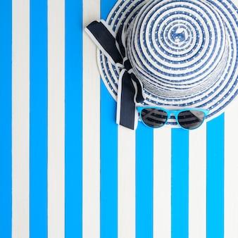 Chapeau rayé et lunettes de soleil sur fond bleu-blanc. vue de dessus, mise à plat.