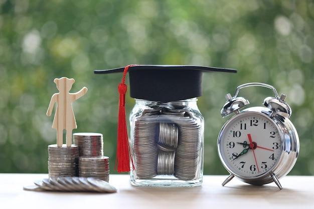 Chapeau de remise des diplômes sur la bouteille en verre et réveil sur fond vert naturel, économiser de l'argent pour le concept d'éducation
