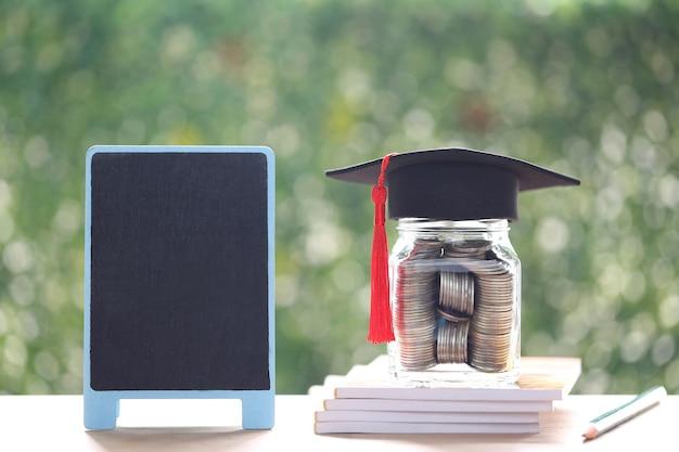 Chapeau de remise des diplômes sur la bouteille en verre et tableau noir sur fond vert naturel, économiser de l'argent pour le concept d'éducation