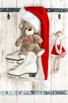 Chapeau rouge du père noël, ours en peluche, ange et patins à glace blancs. décoration de noël de style vintage