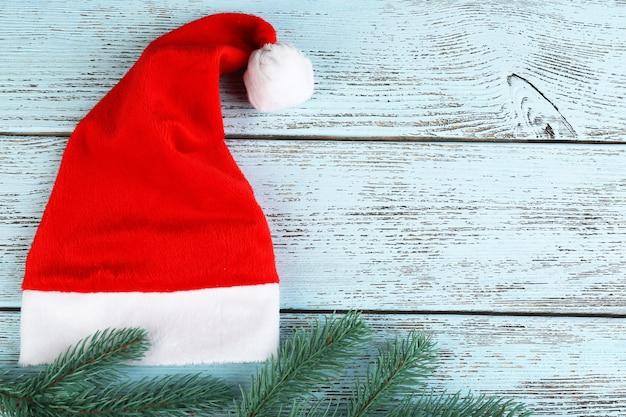 Chapeau rouge de santa avec la branche de sapin sur le fond en bois de couleur