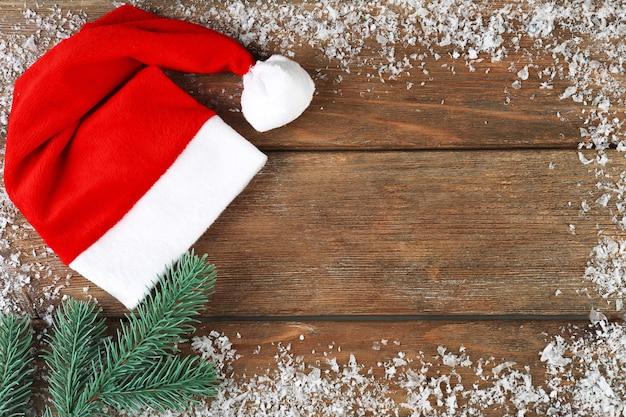 Chapeau rouge de santa avec des flocons de neige et une branche de sapin sur le fond en bois