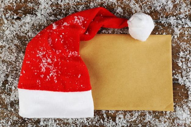 Chapeau rouge de santa avec des flocons de neige et une feuille de papier sur le fond en bois