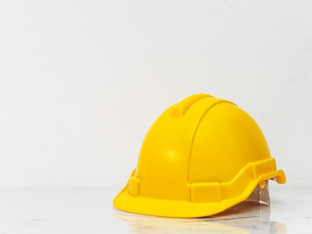 Chapeau de sécurité jaune ingénieur mis sur le dessus de comptoir en marbre blanc