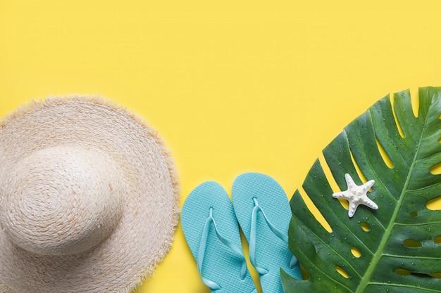 Chapeau de soleil de paille de plage, coquillage et feuilles de monstera. fond de vacances d'été avec accessoires. vue de dessus.