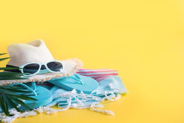 Chapeau de soleil de paille de plage, serviette sur jaune. vacances d'été. fermer.
