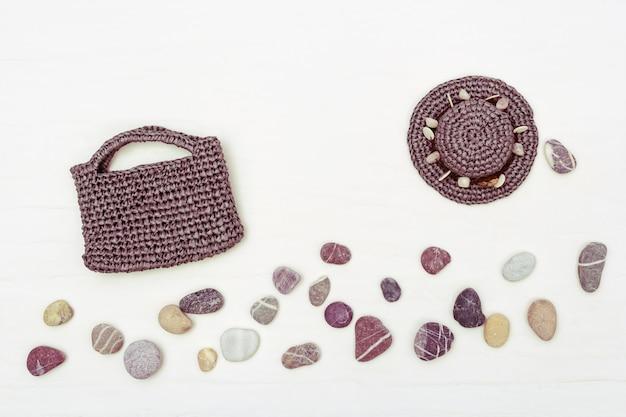 Chapeau de soleil, sac de plage et pierres de la mer. tenue de vacances à la plage. été plat poser.