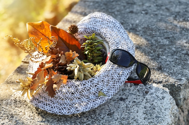 Chapeau de soleil sur trottoir en béton à l'extérieur, avec différentes feuilles et brindilles à l'intérieur et lunettes de soleil