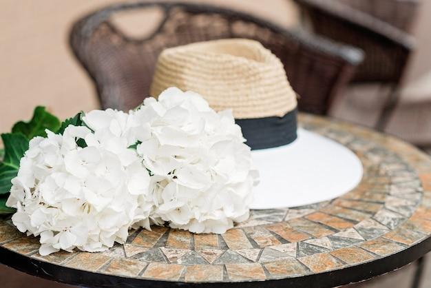 Chapeau solitaire et fleurs d'hortensia blanches sur une table en pierre. fond romantique de printemps et d'été. mise au point sélective douce.