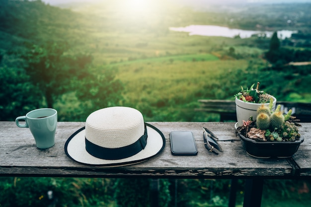 Chapeau, tasse, lunettes de soleil et smartphone sur une table