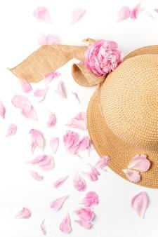 Chapeau tressé de paille, fleurs de pivoine rose et pétales sur blanc, vue de dessus.