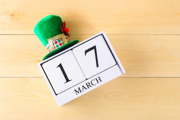 Un chapeau vert sur une table en bois. saint patrick. un calendrier en bois montrant le 17 mars.