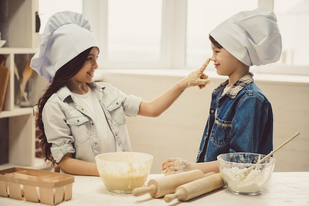 Les chapeaux de chef sourient en cuisinant dans la cuisine.