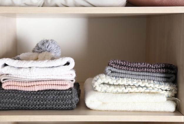 Chapeaux et écharpes chauds sur l'étagère de la penderie