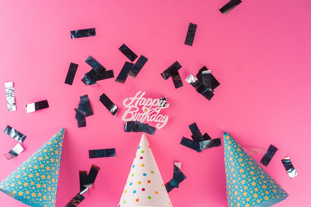 Chapeaux de fête avec guirlandes et plaque signalétique joyeux anniversaire