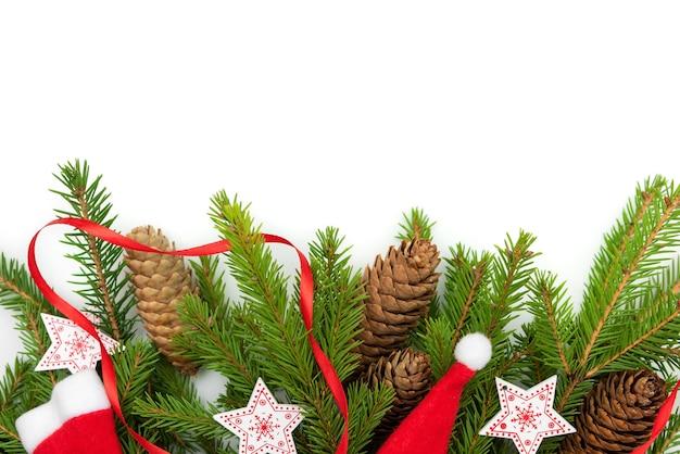 Chapeaux de noël avec des branches de sapin et des étoiles sur fond blanc.