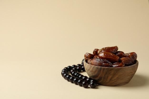 Chapelet et bol avec dates sur surface beige