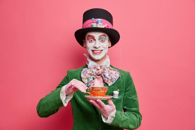 Chapelier masculin positif apprécie le thé habillé en chapeau et veste de velours vert pose contre le mur rose ressemble à un vrai gentleman