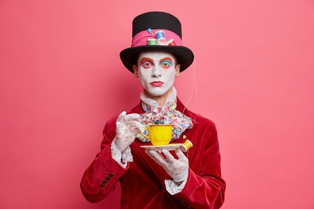 Chapelier de personnage de fiction sérieux avec du maquillage coloré boit du café a le visage blanc habillé en costume d'halloween regarde sérieusement la caméra isolée sur le mur rose