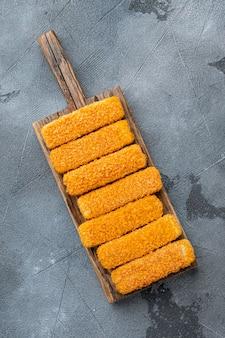 La chapelure de poisson congelé sur une planche à découper en bois sur fond gris vue de dessus à plat