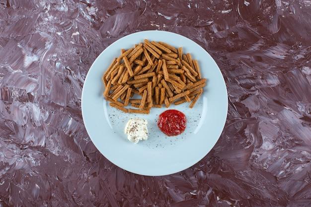 Chapelure avec sauces sur une assiette , sur la table en marbre.