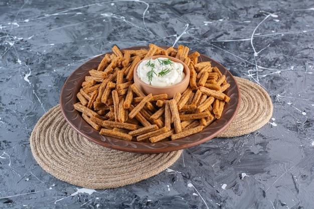 Chapelure et yaourt dans une assiette en bois sur dessous de plat, sur la surface en marbre