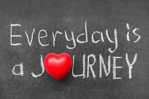 Chaque jour est une phrase de voyage écrite à la main sur un tableau avec le symbole du coeur au lieu d'o