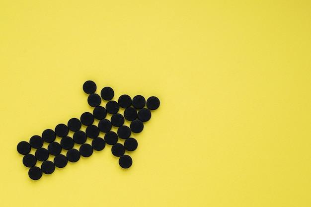 Charbon actif médical sous la forme d'une flèche sur fond jaune. t
